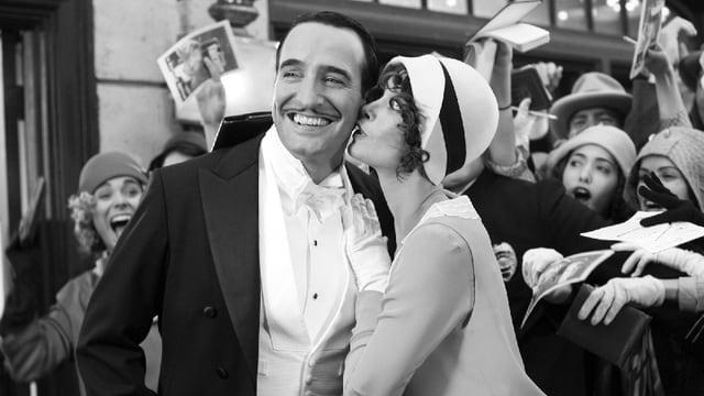 Jean Dujardin im Frack wird von einer Horde junger Damen umringt, die um ein Autogramm bitten. Neben ihm steht Bérénice Bejo und küsst ihn auf die Wange.