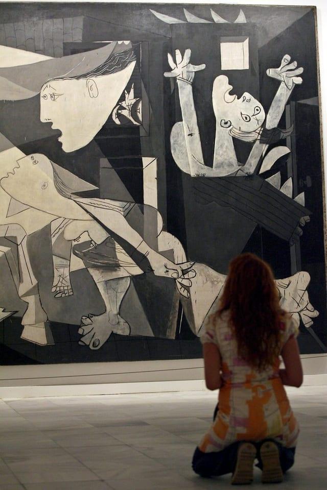 Eine Frau kniet vor Picassos «Guernica».