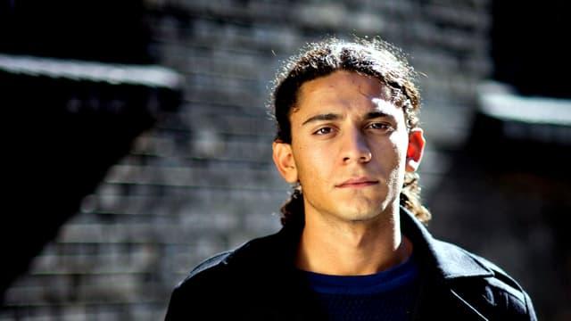 Porträt von Yahya Hassan, der einen schwarzen Mantel trägt und mit ernstem Blick in die Kamera schaut.