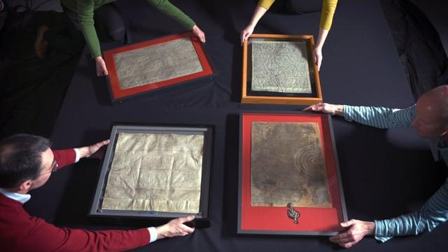 Vier Menschen halten je einen Bilderrahmen mit einem alten Dokument zusammen in die Mitte.
