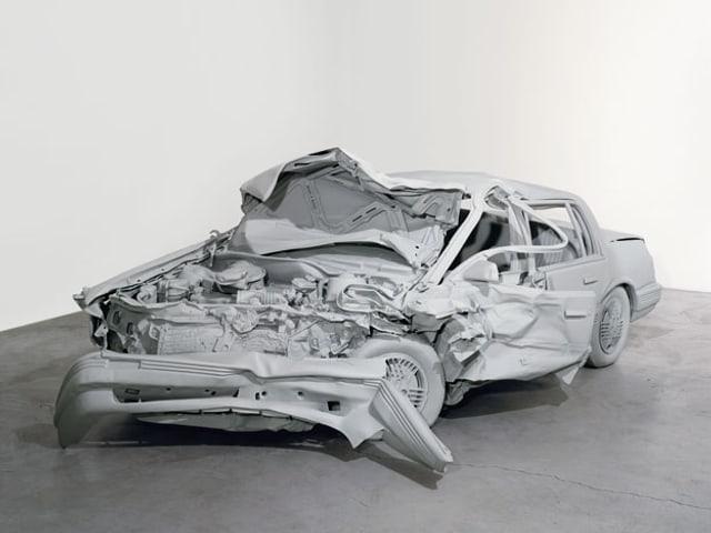 Eine hellgraue Skulptur zeigt ein Auto, dessen vorderer Teil komplett zerstört ist.