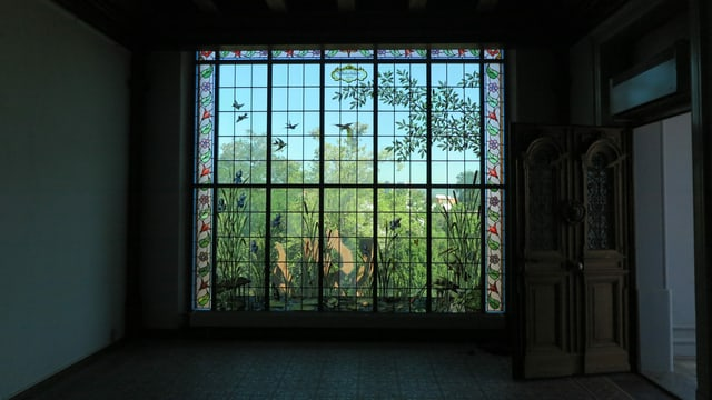 Fenster mit Malereien, daneben führt schwere Holztüre ins Freie
