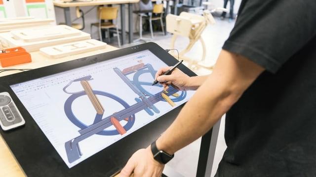Ein Student arbeitet auf einem grafischen Tablet an einem Design.