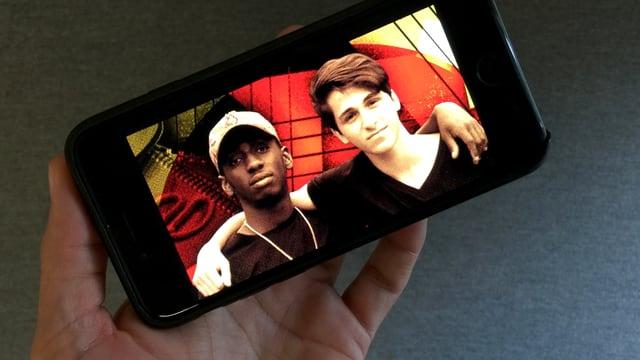 Zwei junge Männer auf dem Display eines Smartphones.