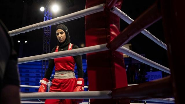 Eine Frau mit Kopftuch steht im Boxring.