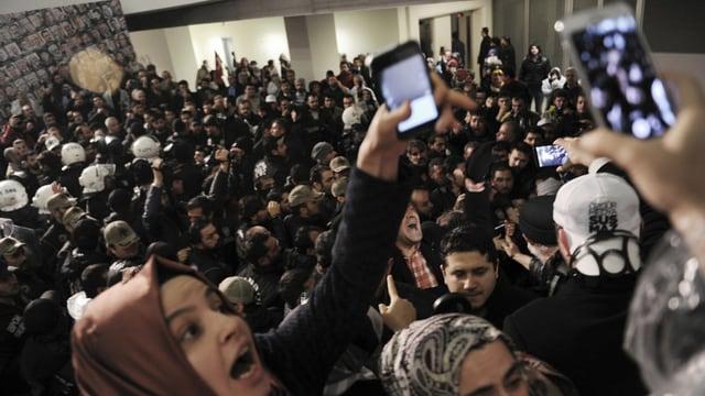 massa persunas che protesteschan, la polizia emprova da tegnair enavos la glieud