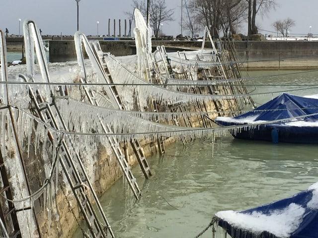 Boote in einem Hafen sind mit Schnee bedeckt. Die Taue sind mit Eiszapfen belegt.