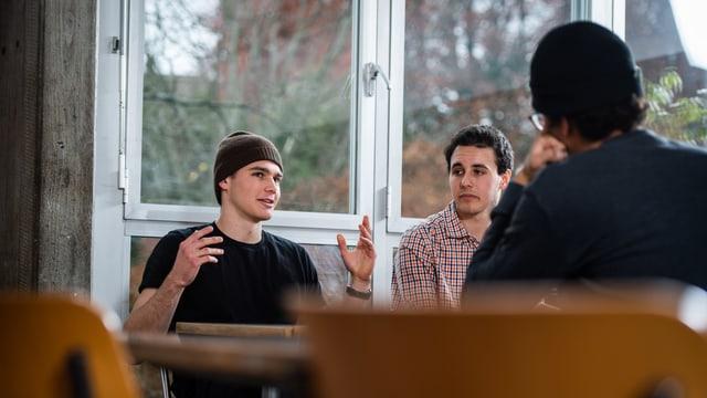 Drei junge Männer an einem tisch. Einer gestikuliert mit den Händen.