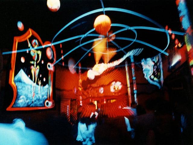 Blick in einen dunklen Raum mit bunt leuchtenden Deko-Elementen.