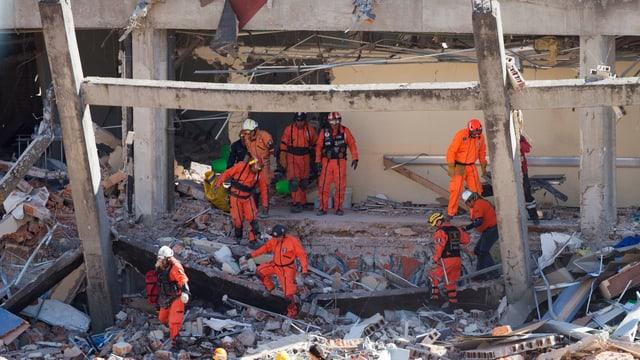 Feuerwehrleute suchen in Trümmern nach Verschütteten.