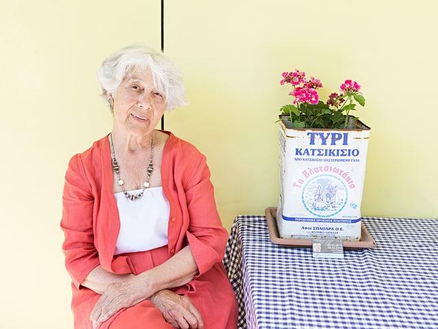 Areti Guioulami an einem Tisch mit blaukariertem Tischtuch. Auf dem Tisch ist eine Pflanze und ein GA.