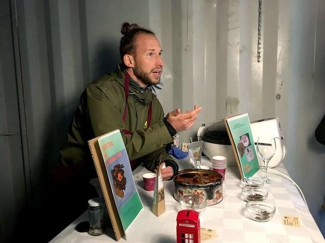 Junger Mann mit seinen Esswaren aus Insekten und Kochbüchern an einem Tisch