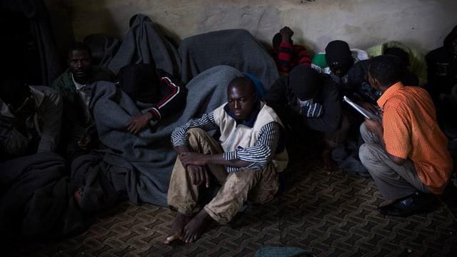 Migranten decken sich mit Decken zu, nachdem sie bei der Flucht übers Mittelmeer aufgefangen wurden.