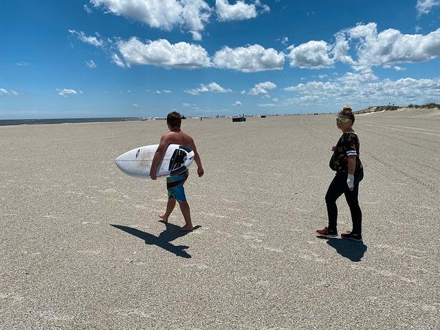Ein Mann mit einem Surfboard am Strand.