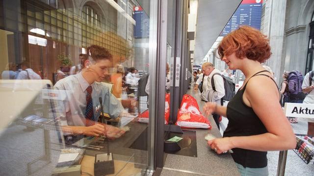 Eine Frau wird an einem Billettschalter der SBB im Hauptbahnhof Zürich bedient.