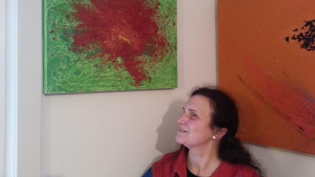 Pina Dolce im Profil fotografiert, vor einem abstrakten, grünen Bild, mit roter Farbe in der Mitte.
