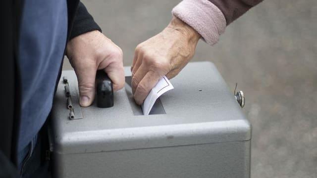 Purtret d'ina urna ed ina dunna che bitta en la brev da votaziun.