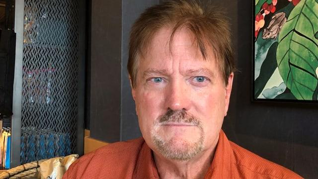 Mann mit Bürstenhaarschnitt, Bart und orangen Hemd.