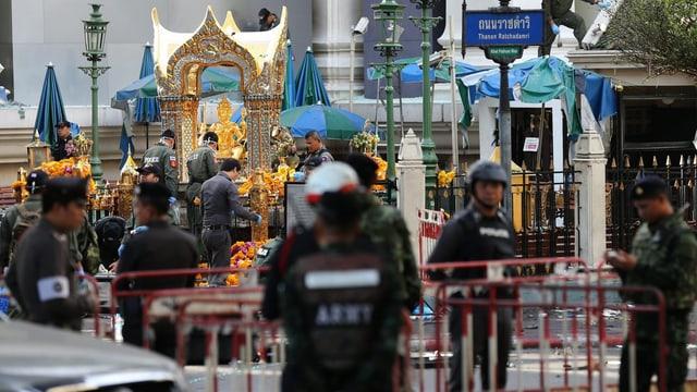 Sicherheitskräfte, Absperrungen, im Hintergrund ein goldener Schrein.