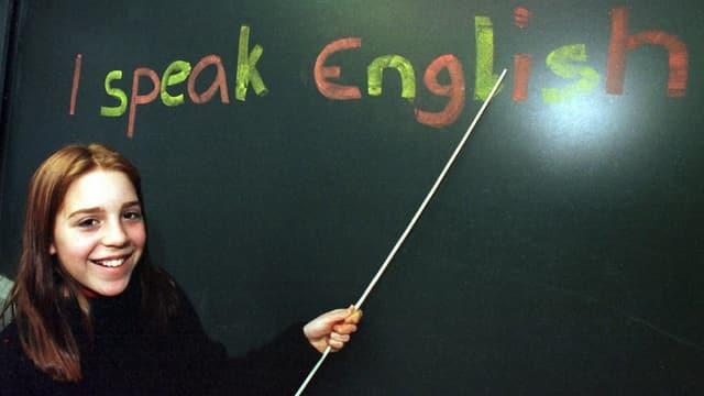 Mädchen vor einer Wandtafel. Darauf steht: I speak english.