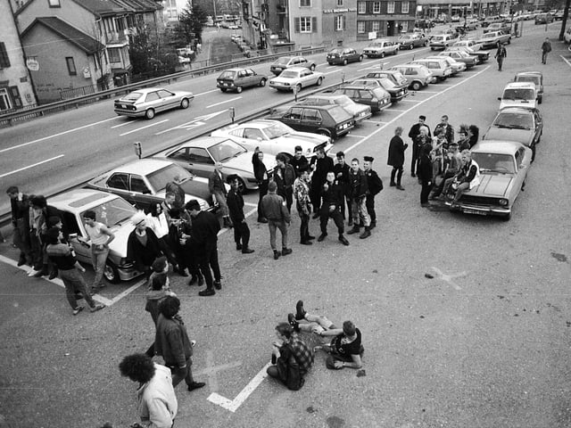 Eine Gruppe Punks sitzt auf dem Parkplatz vor der Grabenhalle.