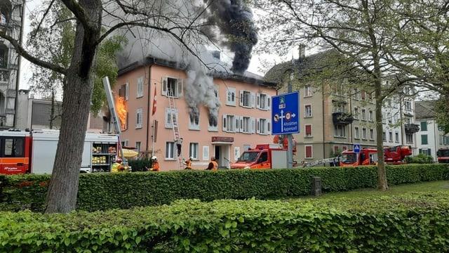 Rauch steigt aus dem Gebäude, die Feuerwehr ist im Einsatz.