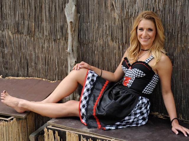Hertel in rockig-angehauchtem Dirndl sitzt gemütlich auf einer improvisierten Holzbank und streckt die Beine von sich.