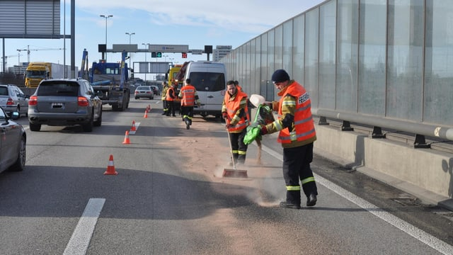 Zwei Feuerwehrmänner streuen nach dem Unfall Bindemittel auf den Ölfleck