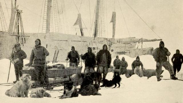 Altes Foto: Männer in Winterkleidung im Schnee neben Hundeschlitten. Im Hintergrund ein grosses Segelschiff.