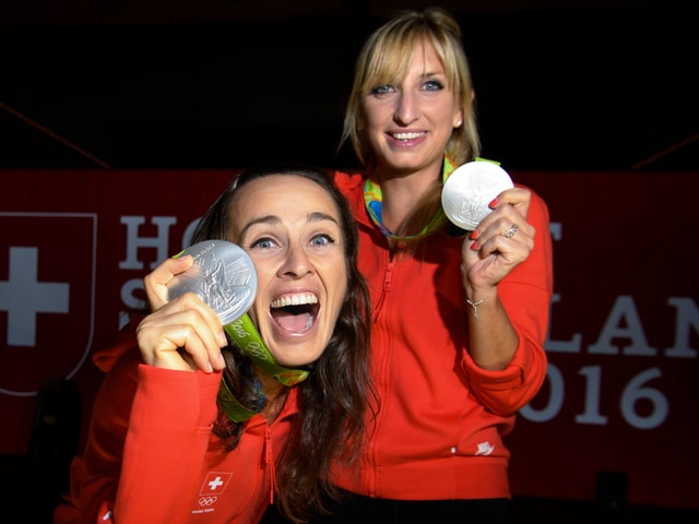 Martina Hingis und Timea Bacsinszky strecken ihre Silbermedaillen der Kamera entgegen.