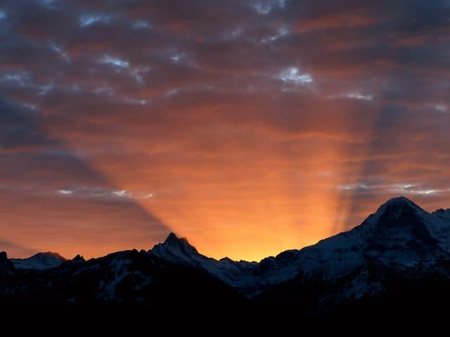 Unten Konturen von Schneebergen, der Himmel ist bewölkt und die Sonne scheint hinter der Bergkette. Helle Strahlen brechen über die Krete.