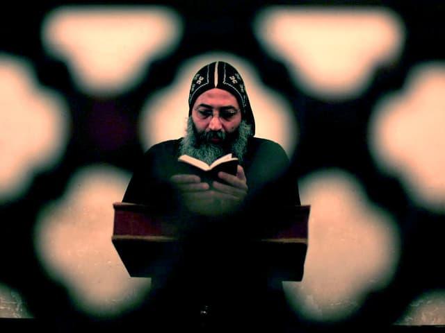 Ein bärtiger Priester betet mit der Bibel in der Hand hinter einer ornamental verzierten Mauer.