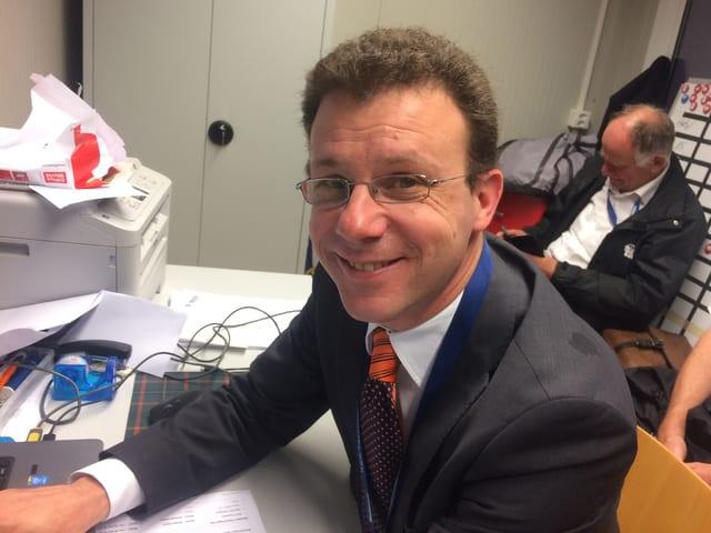 Ein Mann mit Brille sitzt an einem Schreibpult und lacht in die Kamera.