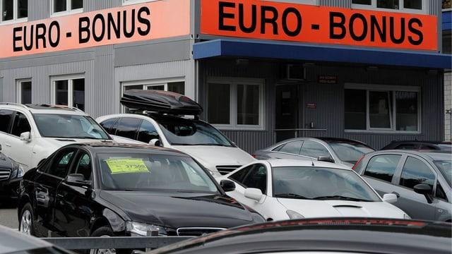 Abgebildet ist eine Garage mit Neuwagen und einem Euro-Bonus-Transparent
