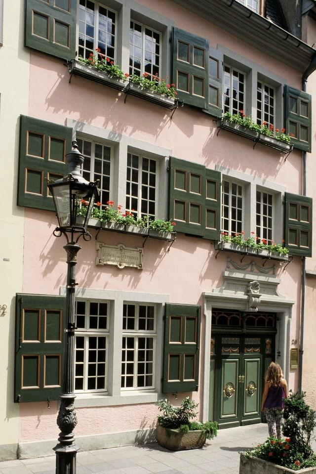 Eine Frau steht vor einem alten Haus