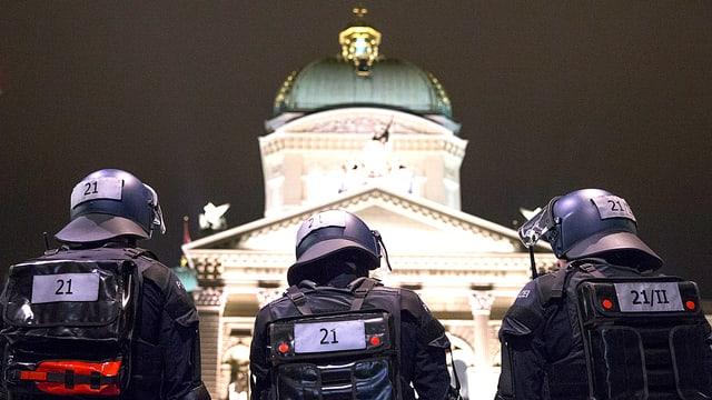 Einsatzbeamte in Kampfmontur stehen auf dieser Nachtaufnahme mit dem Rücken zur Kamera vor dem Bundeshaus in Bern.