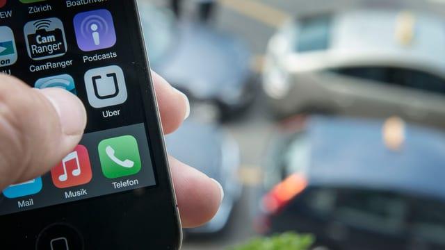 Auf einem Smartphone sieht man einen Finger, der auf die Uber-App drückt