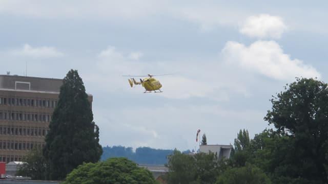 Ein  gelber Helikopter vom TCS setzt zur Landung auf das Kantonsspital Aarau an. Im Hintergrund Wolken, im Vordergrund Bäume.