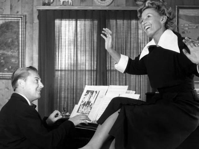 Frau sitzt auf Klavier auf dem ihr Mann ein Lied spielt.