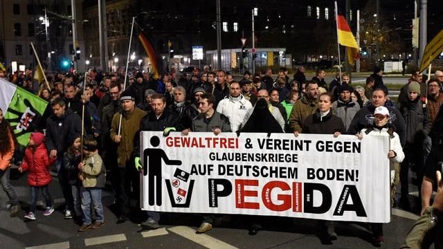 Pegidademonstration in Dresden; viele Menschen um ein Transparent mit Pegida-Schriftzug.