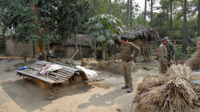 Polizisten stehen auf einem Dorfplatz in Indien.