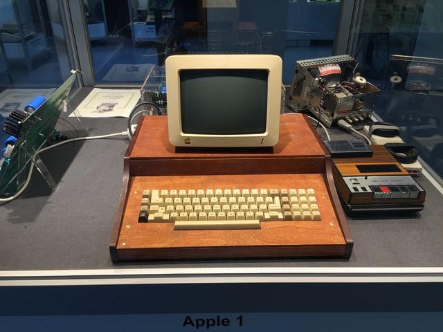 Alter Computerbildschirm auf Holzgestellt, darunter Tastatur, rechts daneben ein Kassettengerät