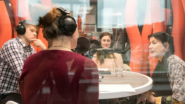 Drei Frauen und ein Mann sitzen mit Kopfhörern in einem Radiostudio und diskutieren.