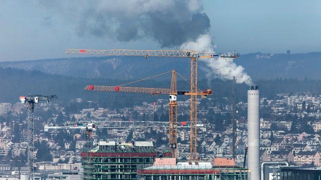 Ein Schornstein raucht, im Hintergrund liegt die Stadt Zürich.