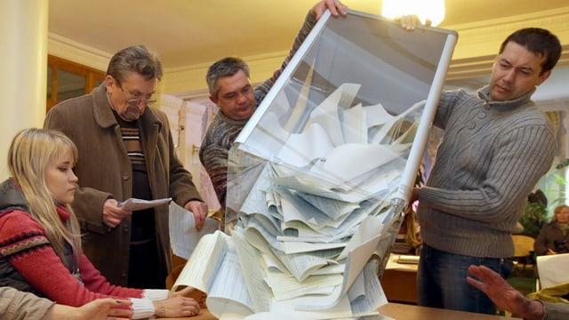 Stimmzettel werden auf einen Tisch geleert.