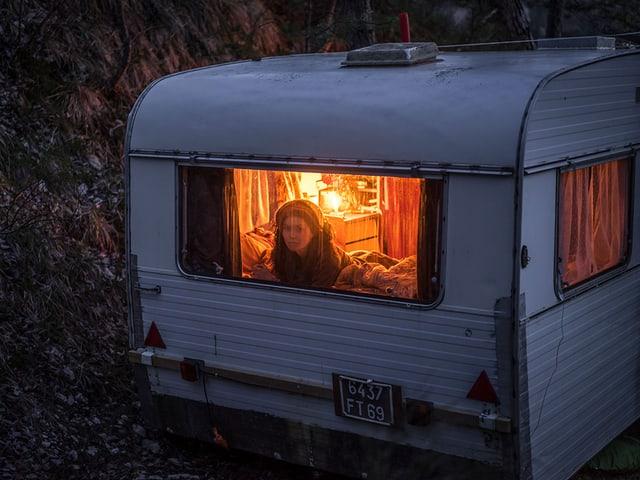 Ein Wohnwagen in der Dunkelheit, eine Frau schaut aus dem erleuchteten Fenster.