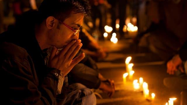 Mehrere Personen beten vor auf dem Boden stehenden Kerzen