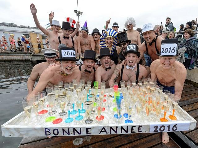 Ein paar Menschen in Badehosen präsentieren die gefüllten Gläser.