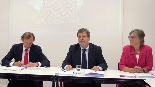 Eine Frau und zwei Männer an einer Medienkonferenz.