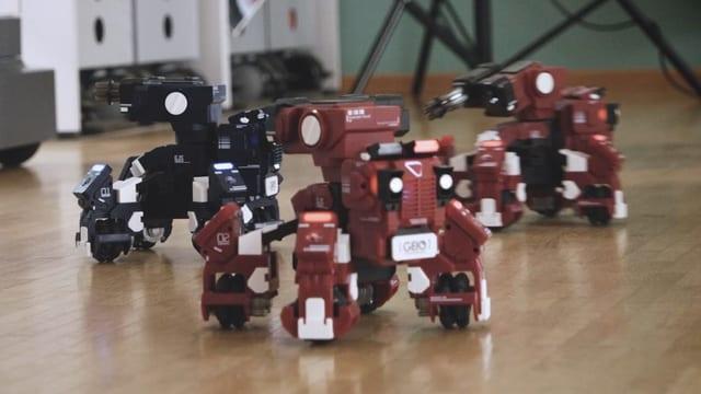 Drei vierfüssige Roboter im Kampf.
